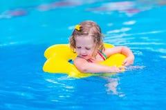 Criança que tem o divertimento em uma piscina Imagens de Stock