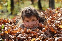 Criança que tem o divertimento exterior durante a queda fotos de stock