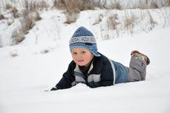 Criança que tem o divertimento na neve Fotografia de Stock Royalty Free