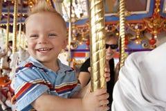 Criança que tem o divertimento no Merry-Go-Round imagem de stock