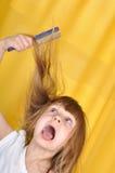 Criança que tem o problema com escovadela de seu cabelo Fotos de Stock