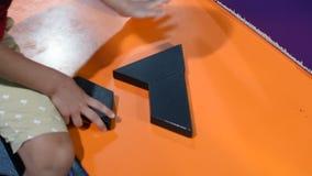 Criança que termina umas três partes para formar formas moventes de um enigma do triângulo em torno de demonstrar o pensamento e  vídeos de arquivo