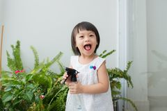 Criança que toma das plantas Spr molhando da menina bonito primeiro Fotos de Stock Royalty Free