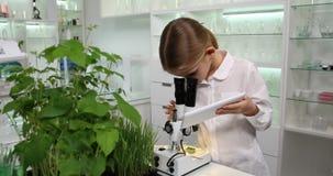 Criança que usa o microscópio no laboratório de química da escola, estudante que estuda, experiências 4K filme