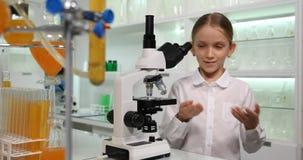 Criança que usa o microscópio no laboratório de química da escola, trabalhando no projeto científico 4K filme