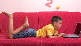 Criança que usa o portátil Fotos de Stock Royalty Free