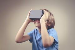 Criança que usa a realidade virtual nova, vidros do cartão de VR fotografia de stock