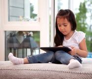 Criança que usa a tabuleta de Digitas Fotografia de Stock