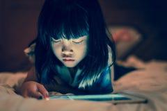 Criança que usa a tabuleta para em linha aprender em casa foto de stock