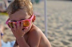 Criança que veste óculos de sol cor-de-rosa Fotografia de Stock Royalty Free