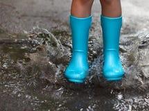 Criança que veste as botas de chuva azuis que saltam em uma poça foto de stock royalty free