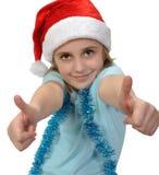 Criança que veste um chapéu de Santa com polegares acima Fotos de Stock Royalty Free