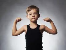 Criança Rapaz pequeno engraçado mostrando seus músculos do bíceps da mão foto de stock