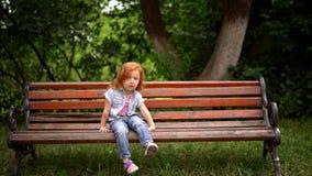 A criança readheaded de sorriso senta-se em um banco de parque filme