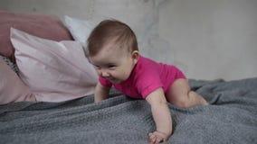 Criança recém-nascida alegre que rasteja na cama filme