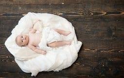 Criança recém-nascida com os olhos curiosos azuis no fundo de madeira foto de stock royalty free
