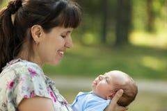 Criança recém-nascida de sono bonito do bebê nas mãos da mãe Imagens de Stock