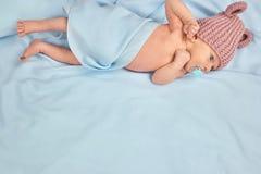 Criança recém-nascida na cama com o chapéu da chupeta e das lãs Fotografia de Stock