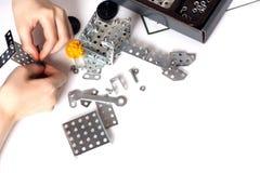 A criança recolhe as peças de metal do jogo modelo da criança imagens de stock royalty free