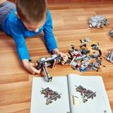 A criança recolhe o jogo de construção plástico do brinquedo fotografia de stock royalty free