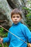 Criança séria com uma espada de madeira na madeira imagens de stock royalty free