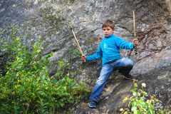 Criança séria com uma espada de madeira na pedra foto de stock royalty free