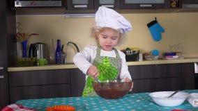 Criança séria da menina com massa de mistura da colher na bacia de vidro na mesa de cozinha video estoque