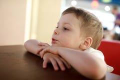 Criança séria no café Imagens de Stock Royalty Free