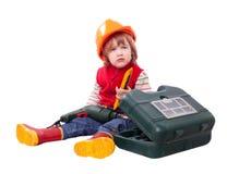 Criança séria no capacete de segurança com ferramentas de funcionamento Foto de Stock