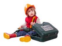 Criança séria no capacete de segurança com ferramentas de funcionamento Fotografia de Stock