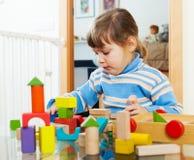 Criança séria que joga com brinquedos Fotografia de Stock