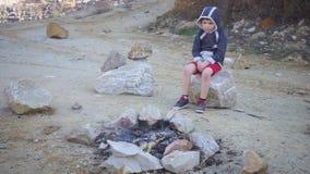Criança só que senta-se pelo fogo nas montanhas vídeos de arquivo