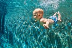 A criança salta debaixo d'água na piscina Imagens de Stock