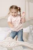 A criança salta na cama Fotos de Stock