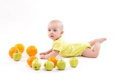 A criança saudável de sorriso bonito encontra-se em um fundo branco entre o frui fotografia de stock royalty free