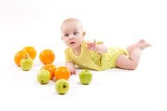 A criança saudável de sorriso bonito encontra-se em um fundo branco entre o frui imagens de stock royalty free