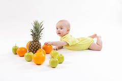 A criança saudável de sorriso bonito encontra-se em um fundo branco entre o frui foto de stock royalty free