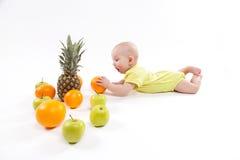 A criança saudável de sorriso bonito encontra-se em um fundo branco entre o frui imagem de stock
