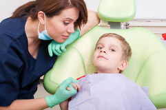 Criança segura e relaxado que senta-se na cadeira do dentista fotos de stock