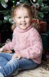 A criança senta-se ao lado de uma árvore de Natal Imagem de Stock