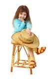 A criança senta-se em uma cadeira de madeira velha com chapéu Fotografia de Stock
