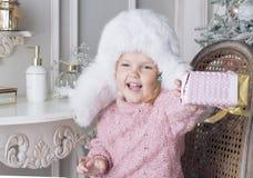 A criança senta-se em uma cadeira e em guardar um presente Imagem de Stock