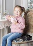 A criança senta-se em uma cadeira e em guardar um presente Foto de Stock Royalty Free