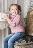 A criança senta-se em uma cadeira e em guardar um presente Foto de Stock