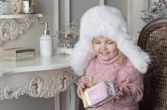 A criança senta-se em uma cadeira e em guardar um presente Fotos de Stock Royalty Free