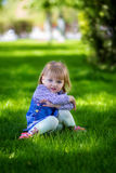 A criança senta-se em uma grama Imagem de Stock Royalty Free