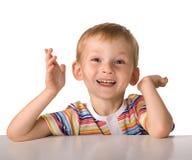 A criança senta-se em uma tabela Imagem de Stock Royalty Free