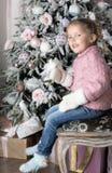 A criança senta-se na cadeira perto da árvore de Natal Imagens de Stock Royalty Free