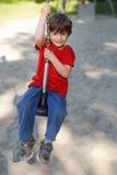 A criança senta-se na corda do balanço Imagens de Stock