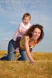 A criança senta-se na mamã Imagem de Stock